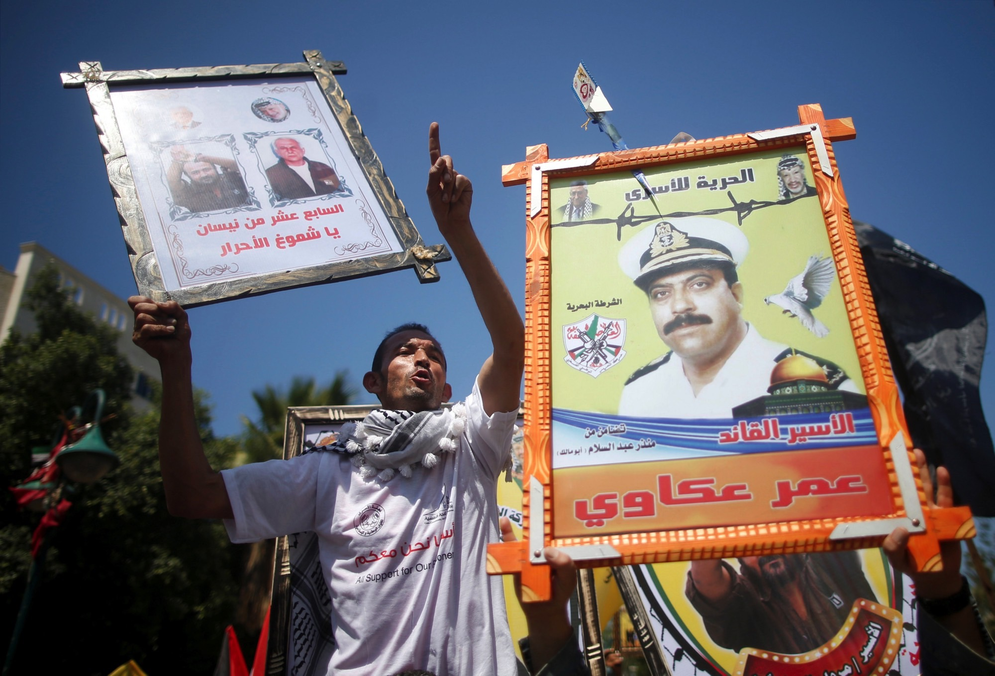Demonstrators hold pictures of jailed Palestinians during a rally in support of Palestinian prisoners on hunger strike in Israeli jails, in Gaza City April 17, 2017. Credit: Reuters/Mohammed Salem
