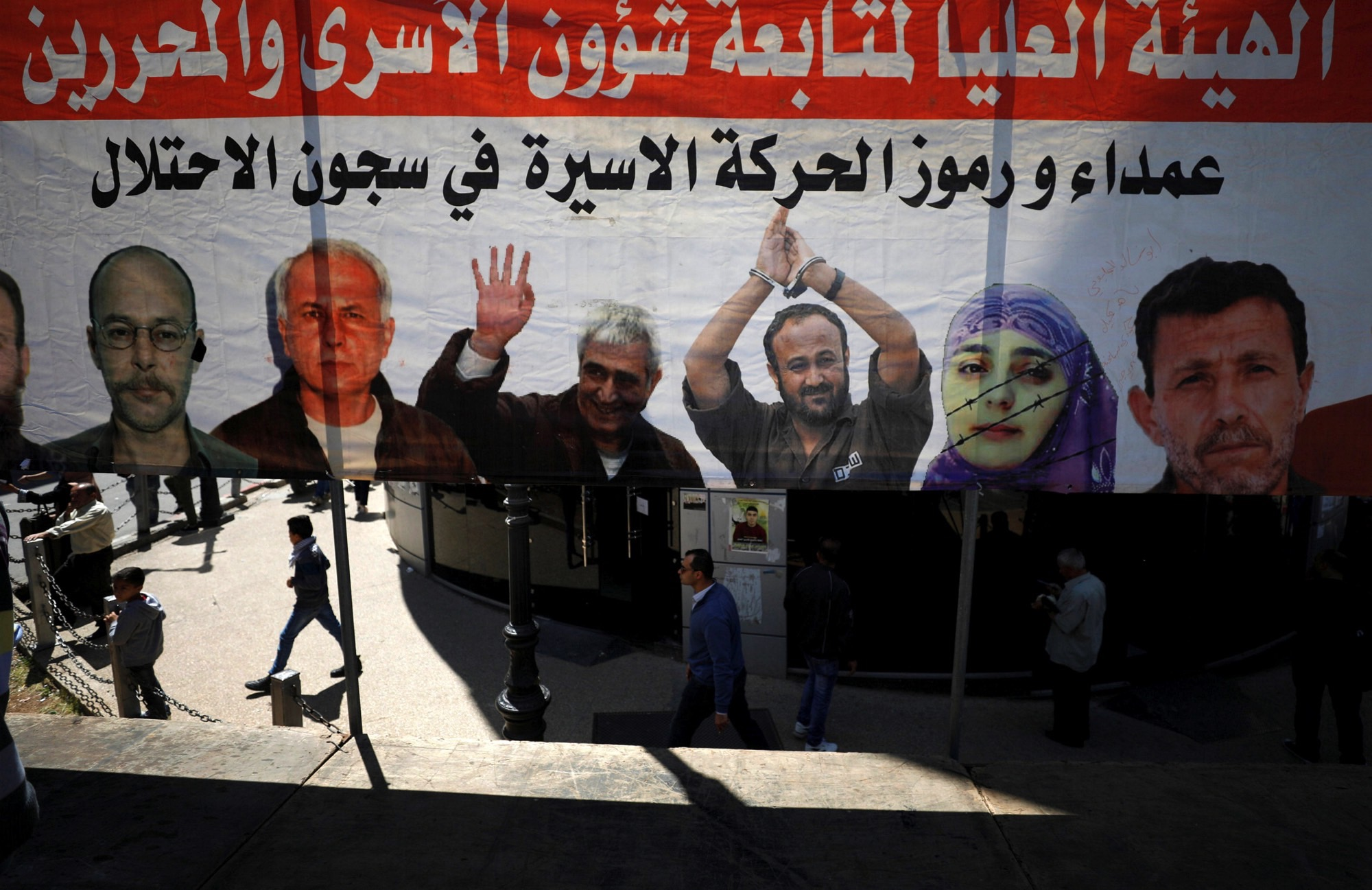 People walk past a poster depicting Palestinian prisoners held in Israeli jails, in the West Bank city of Ramallah April 17, 2017. Credit: Reuters/Mohamad Torokman