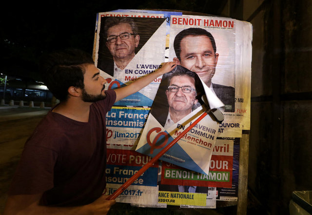 A member of the French far-left Parti de Gauche pastes a poster on a free billboard for French far-left Parti de Gauche candidate Jean-Luc Melenchon over a poster of Socialist candidate Benoit Hamon (top L) as part of the 2017 French presidential election campaign in Nice, France, April 12, 2017. Credit: Reuters/Eric Gaillard