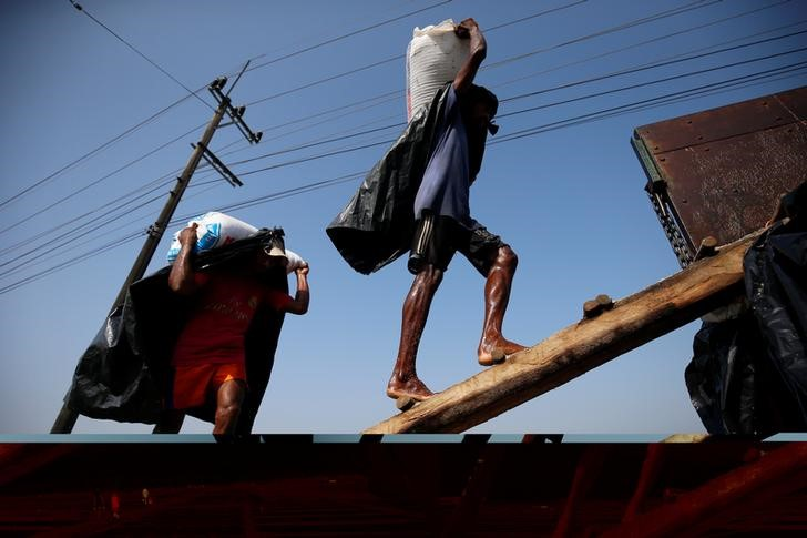 Rohingya refugee workers carry bags of salt as they work in processing yard in Cox's Bazar, Bangladesh. Picture taken on April 12, 2017. Credit: Reuters/Mohammad Ponir Hossain/Files