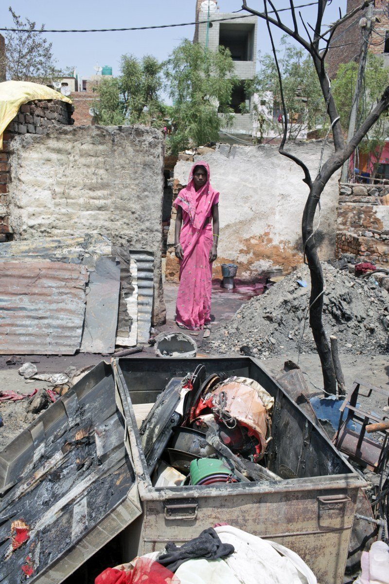 A woman stands in front of her burnt house in Bawana. Credit: Hazards Centre