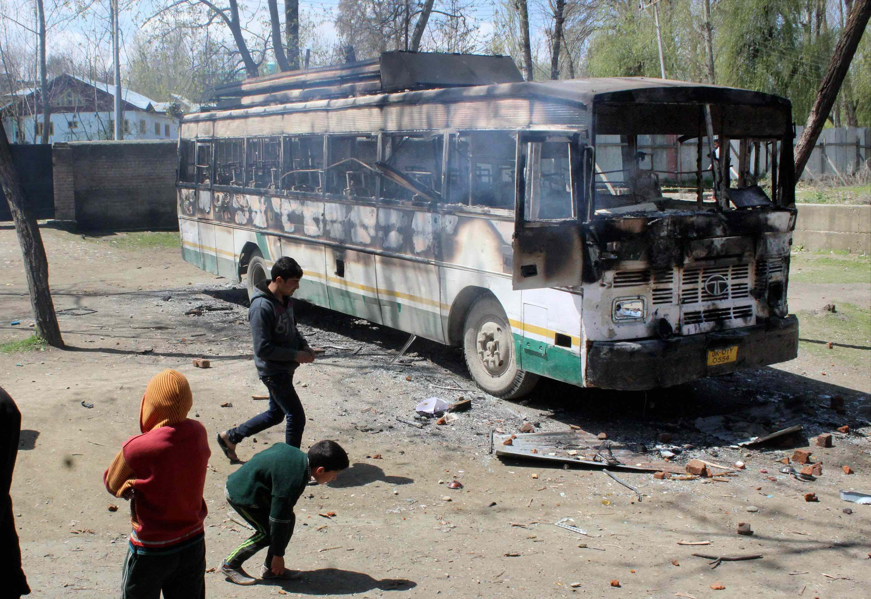 Protesters throwing stones at a burning polling staff bus after they attacked a polling station at Kanihama in Srinagar on Sunday. Credit: PTI