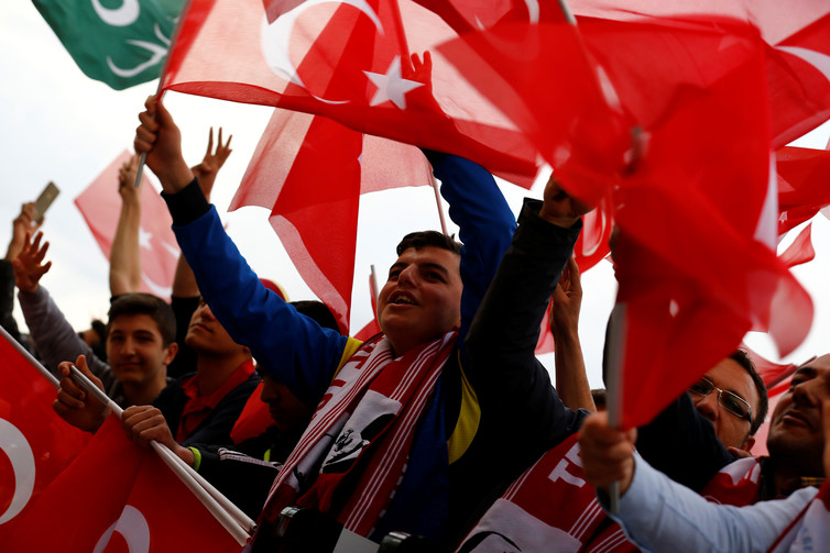 Erdogan's supporters wave national flags as they wait for his arrival at the Presidential Palace after the referendum. Credit: Umit Bektas/Reuters