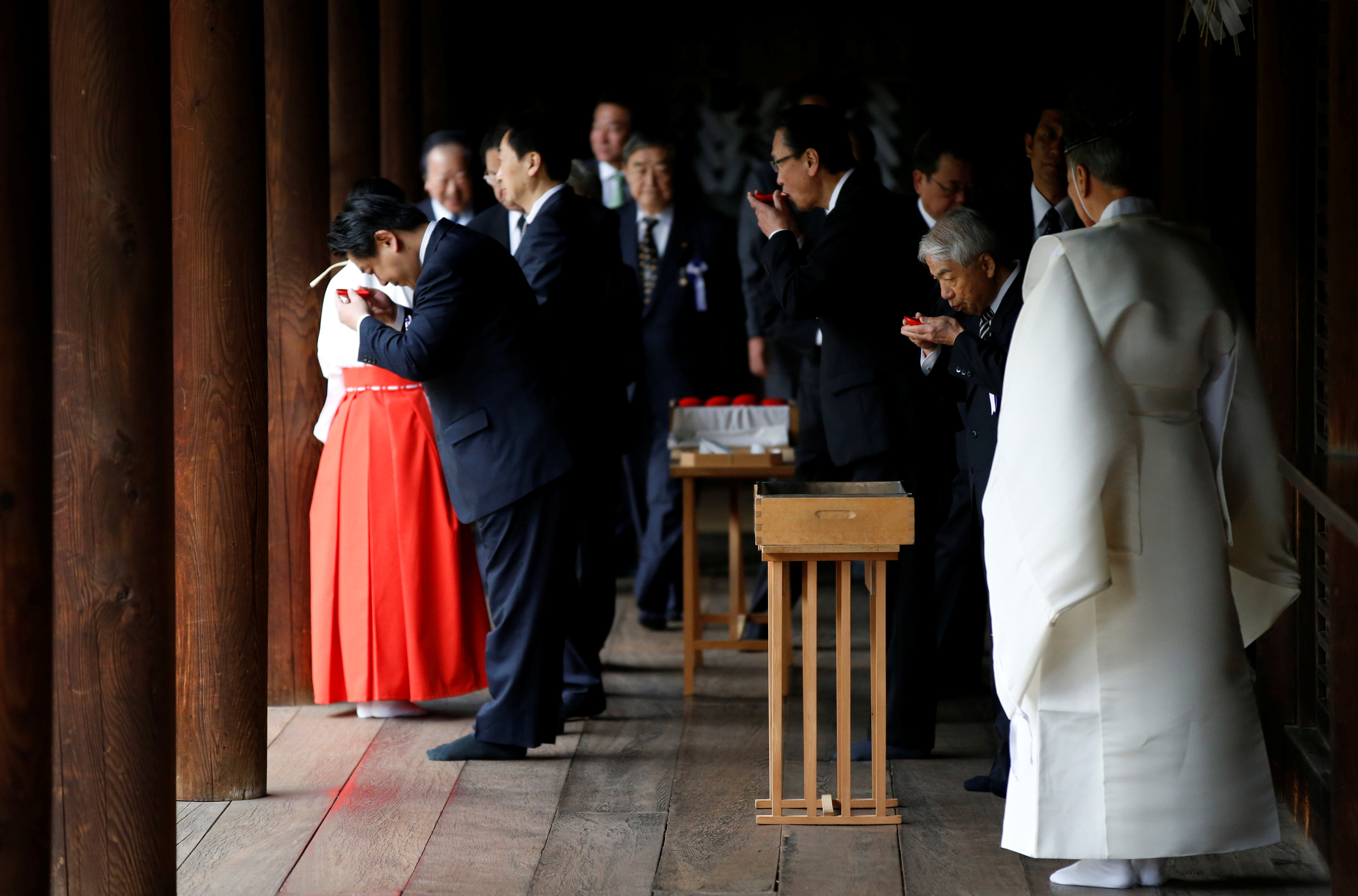 A group of lawmakers including Japan's ruling Liberal Democratic Party (LDP) lawmaker Hidehisa Otsuji (2nd R) sip sake as a ritual after offering prayers at the Yasukuni Shrine in Tokyo, Japan April 21, 2017. Credit: Reuters/Toru Hanai