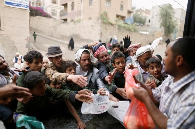 People gather to collect food rations at a food distribution center in Sanaa, Yemen March 21, 2017. Credit: Reuters/Khaled Abdullah