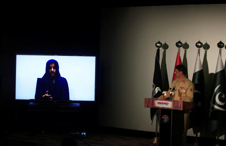 Noreen Leghari, a would-be Islamic State female suicide bomber, is seen in a video confession shown during a news conference by Maj. Gen. Asif Ghafoor, director general of Inter Services Public Relations (ISPR), (R) in Rawalpindi, Pakistan, April 17, 2017. REUTERS/Faisal Mahmood