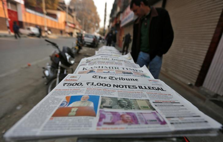 A man looks at newspapers with cover stories on withdrawal of Indian 500 and 1,000 rupee notes from circulation, on a pavement in Srinagar November 9, 2016. Credit: Danish Ismail/Reuters/Files