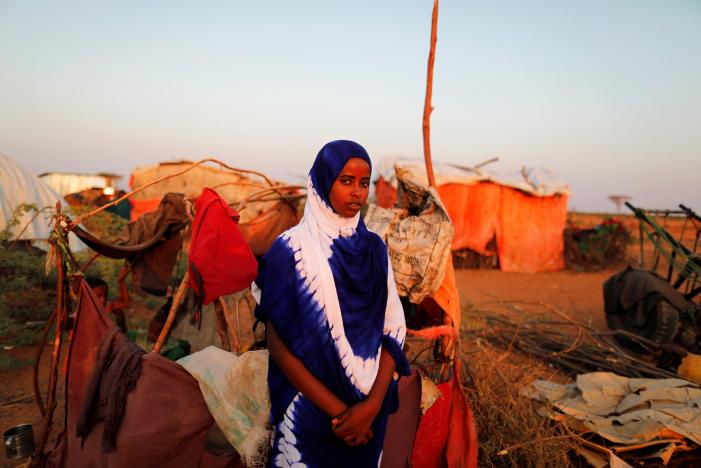 Zeinab, 14, poses for a photograph beside her shelter at a camp for internally displaced people from drought hit areas in Dollow, Somalia April 2, 2017. REUTERS/Zohra Bensemra