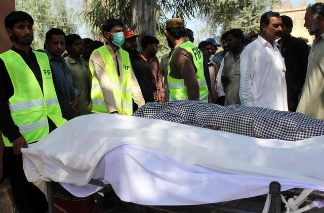 Men gather as rescue workers move the bodies of victims, who were killed in a Sufi shrine, on the outskirts of Sargodha, Pakistan April 2, 2017. Credit: Reuters