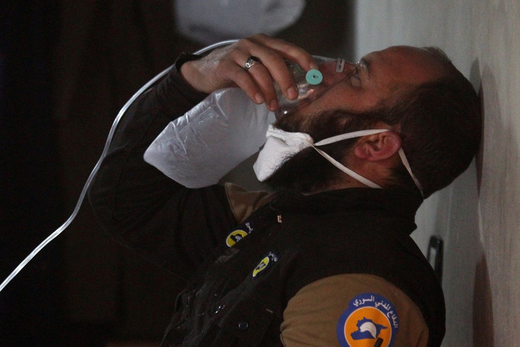 A civil defence member breathes through an oxygen mask after a suspected gas attack in the town of Khan Sheikhoun. Credit:Ammar Abdullah/Reuters
