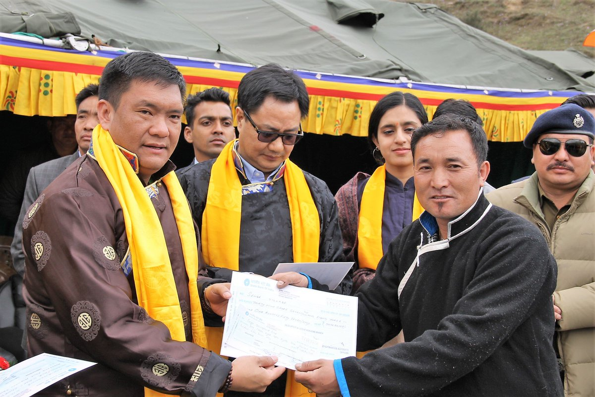 Villagers receiving compensation from chief minister Pema Khandu and Union minister of state for home Kiren Rijiju. Credit: Twitter