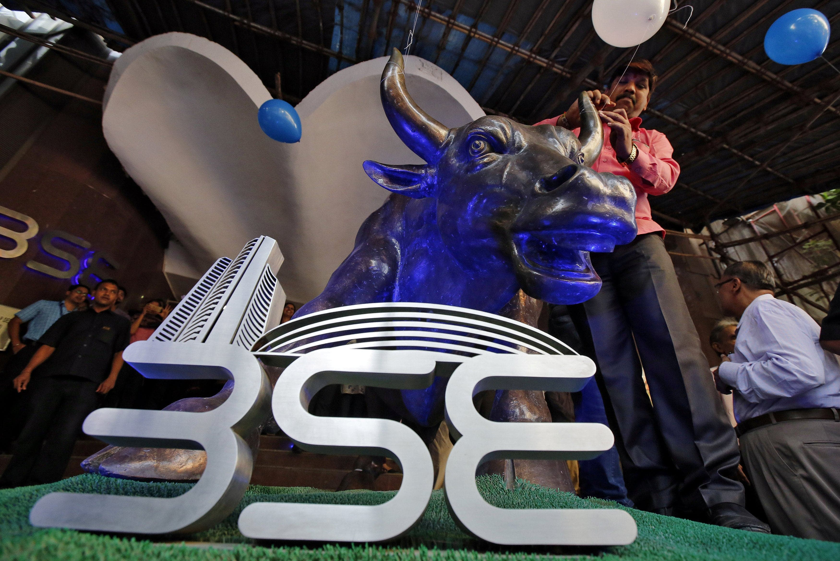 FILE PHOTO: A man ties a balloon to the horns of a bull statue at the entrance of the Bombay Stock Exchange (BSE) while celebrating the Sensex index rising to over 30,000, in Mumbai, India April 26, 2017. Credit: Reuters/Shailesh Andrade/File Photo