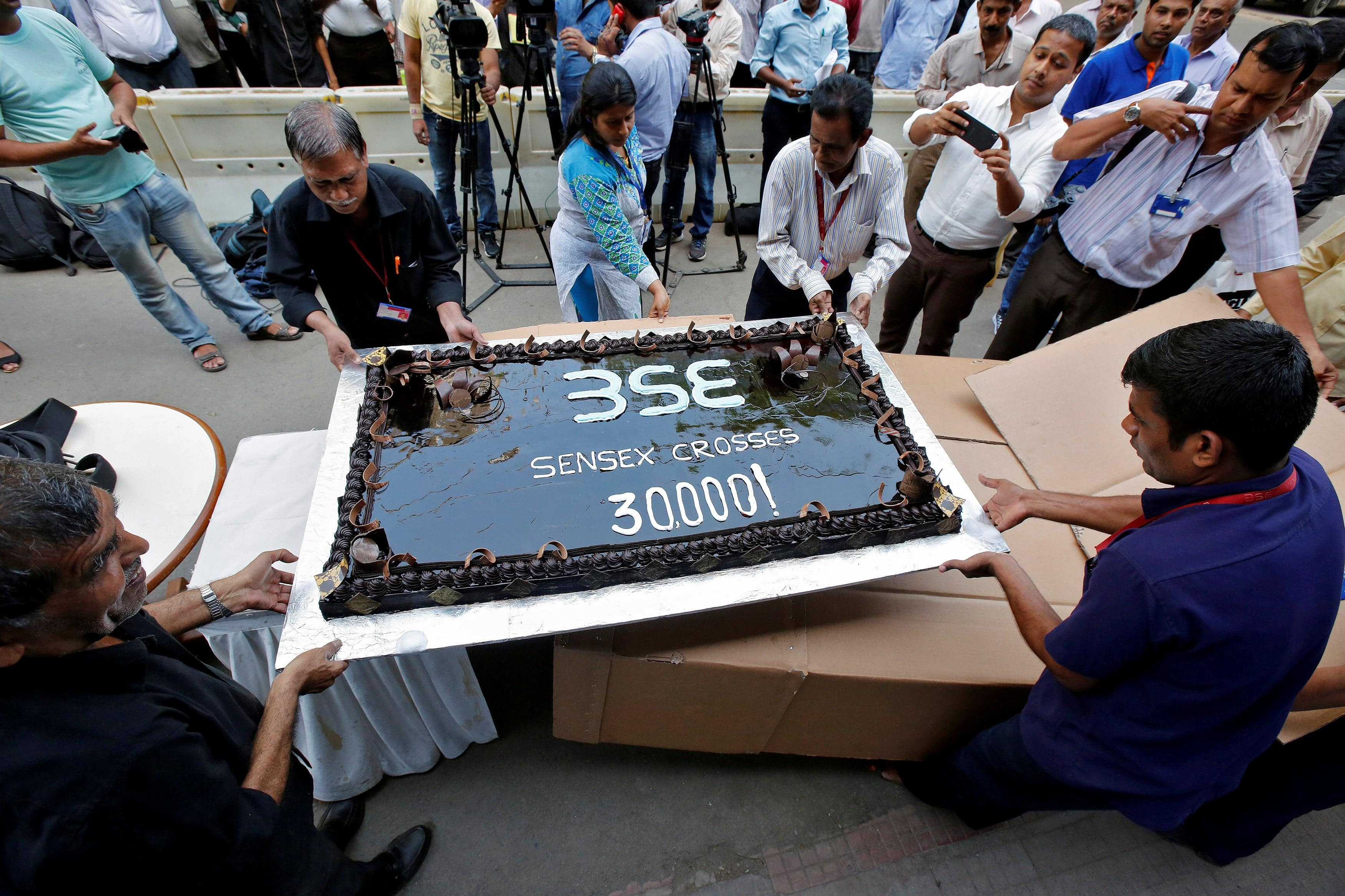 FILE PHOTO: Employees of the Bombay Stock Exchange (BSE) carry a cake outside the building for the celebrations marking the Sensex index rising over 30,000, in Mumbai, India April 26, 2017. REUTERS/Shailesh Andrade/File Photo