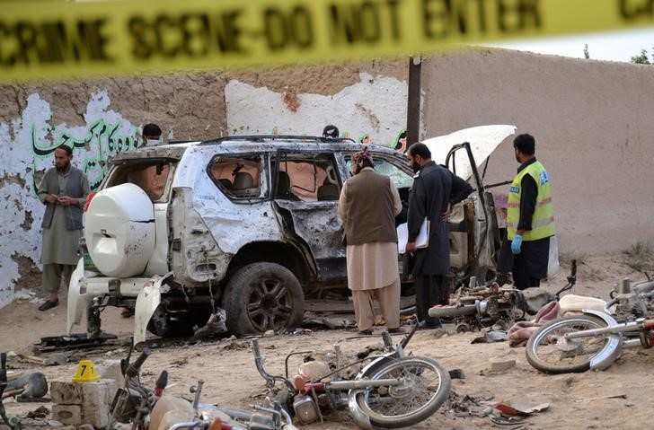 Security officers collect evidence as they investigate crime scene after a bomb exploded next to a convoy of deputy chairman of the Pakistan Senate, Senator Ghafoor Haideri in Mastun