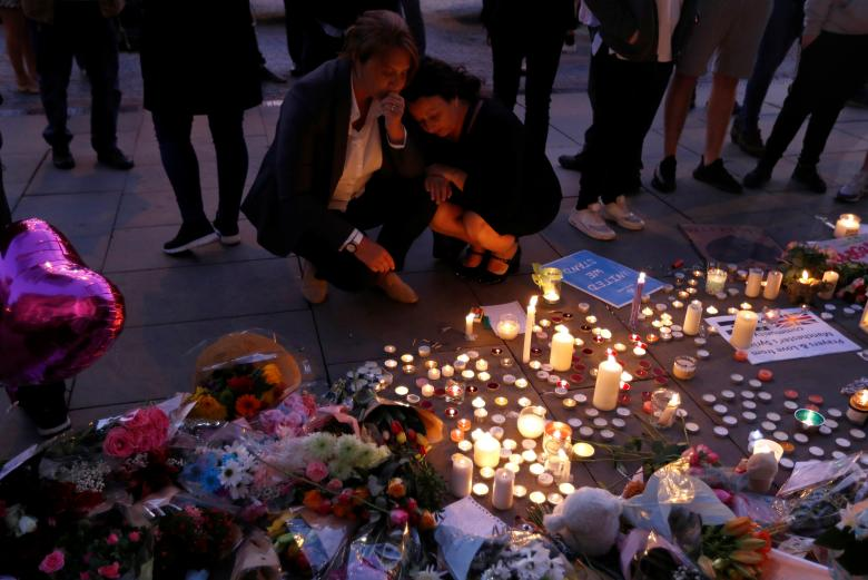 Women pay their respects following a vigil in central Manchester. Credit: Reuters/Peter Nicholls
