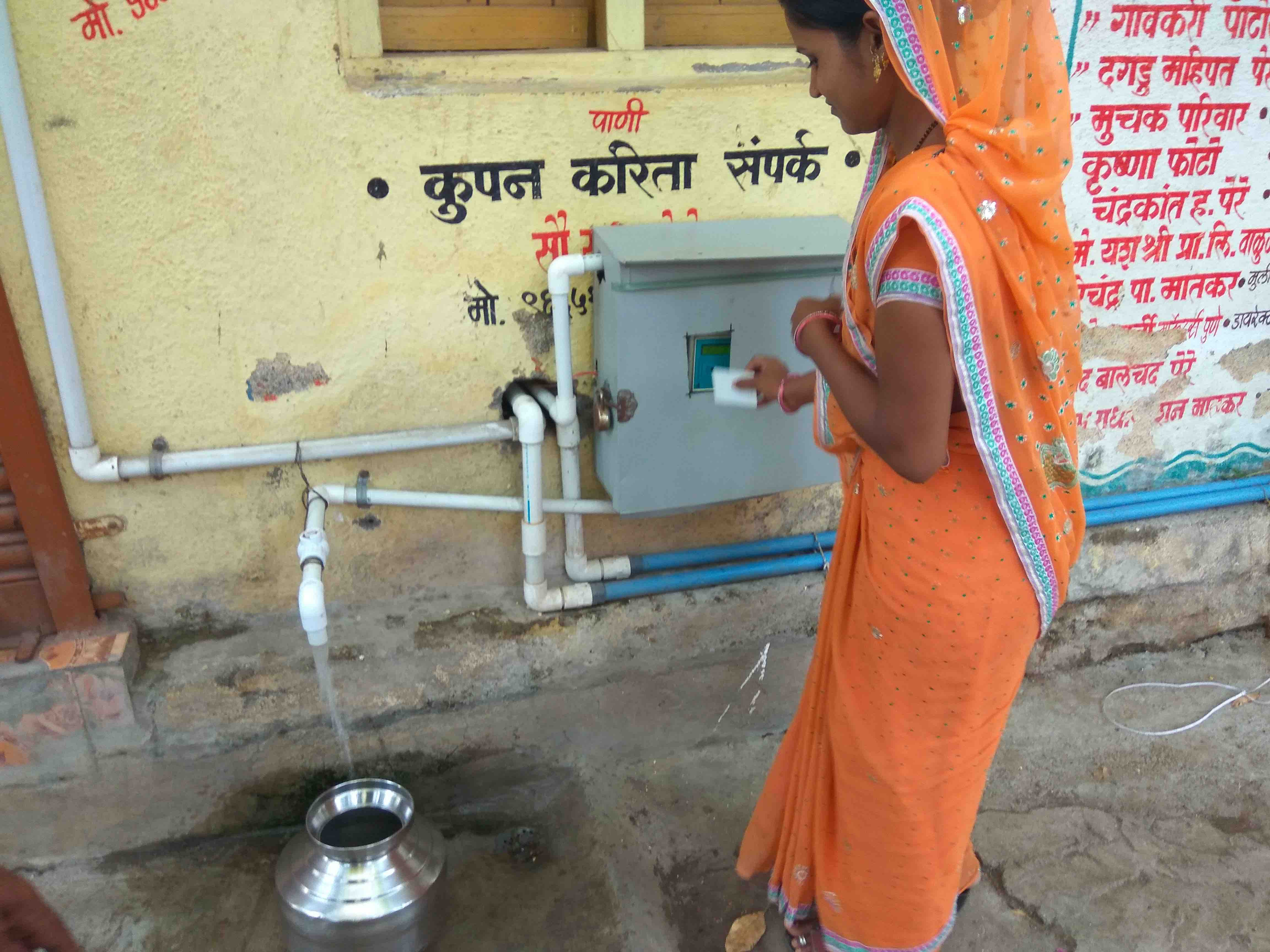 A resident of Patoda village, outside Aurangabad, uses her 'ATM card' to fill a pot with purified drinking water. Credit: Raghu Karnad
