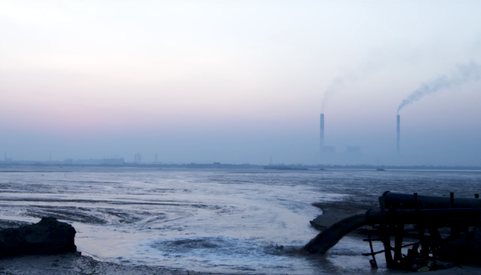 A view of the Seppakkam ash pond, with chimney stacks seen on the horizon. Source: YouTube