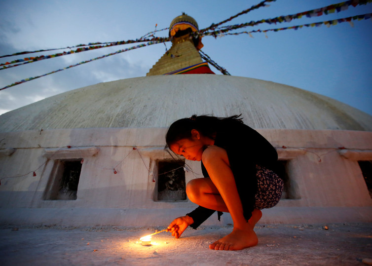 A girl lights a candle as she marks the anniversary of the first 2015 Nepal earthquake, at Boudhanath stupa in Kathmandu. Credit: Reuters/Navesh Chitrakar