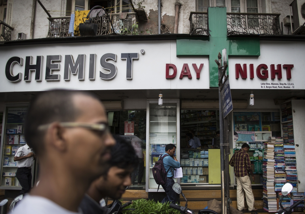 People walk past a chemist shop at a market in Mumbai, India. Credit: Reuters
