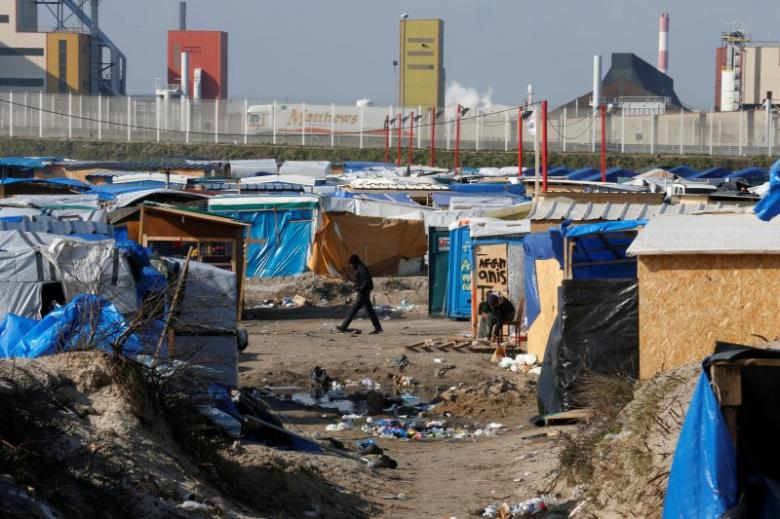 "A migrant walks past makeshift shelters in the northern area on the final day of the dismantlement of the southern part of the camp called the 'Jungle"" in Calais, France, March 16, 2016. Credit: Reuters/Pascal Rossignol"