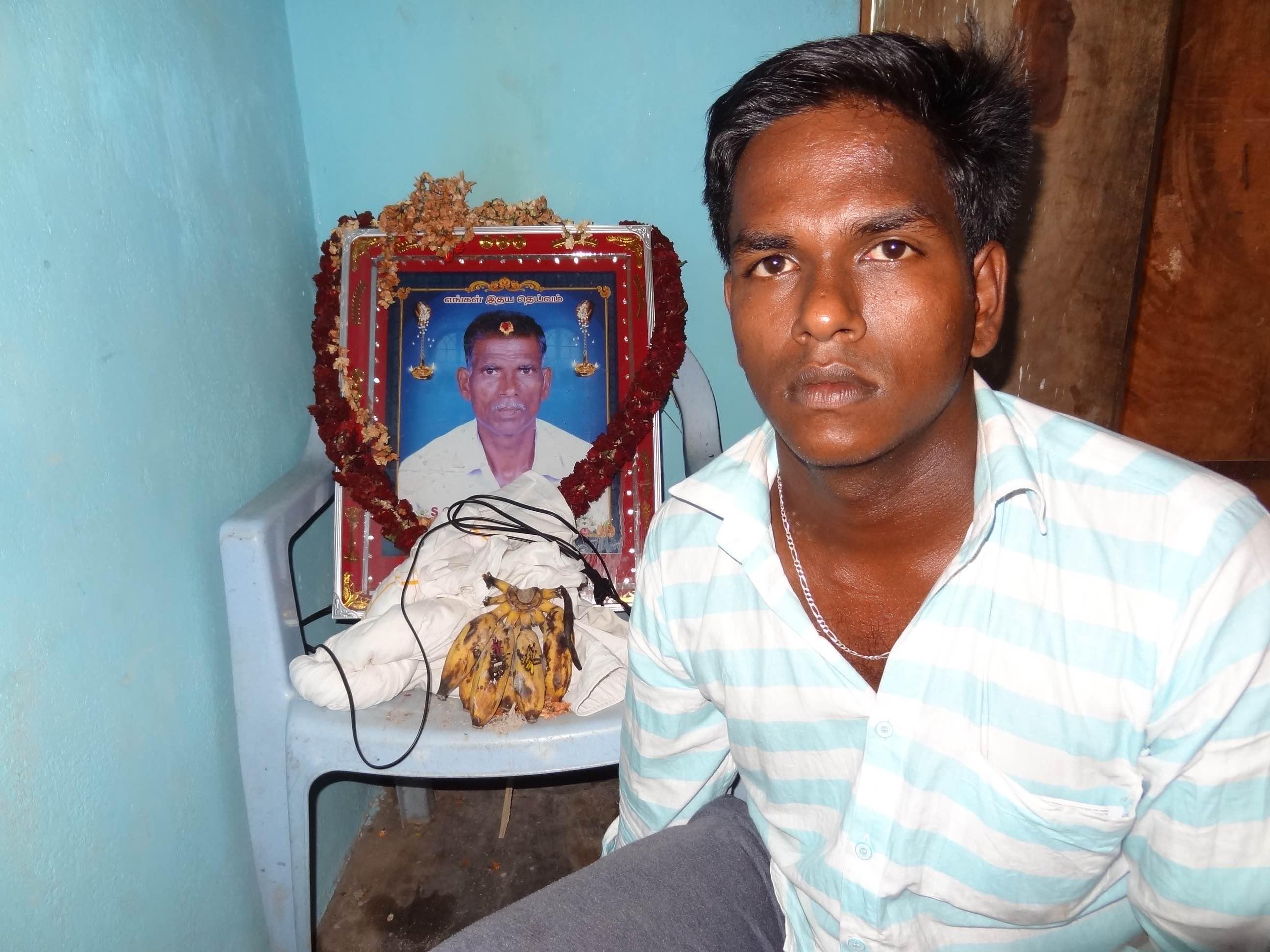 Karti with his father's photograph at their home. Credit: Jaideep Hardikar