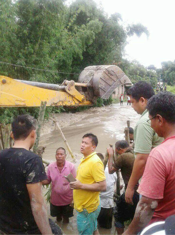 Manipur's PWD minister Th. Biswajit seen with locals repairing a breached embankment. Credit: Twitter