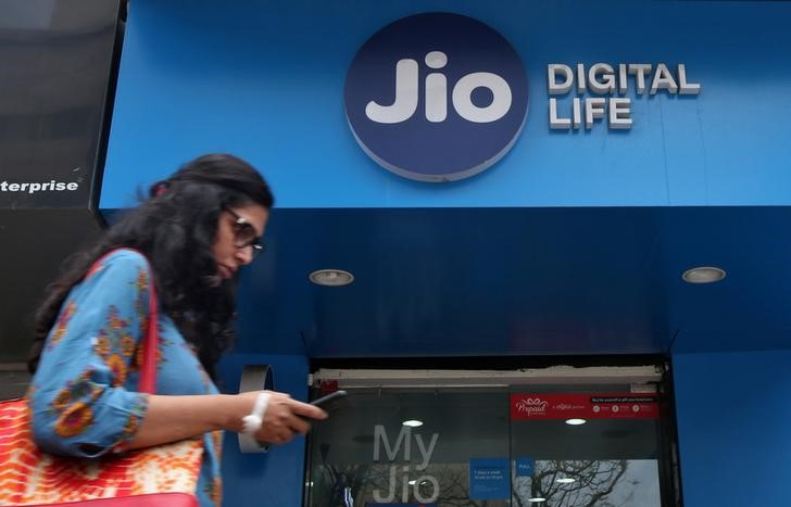 A woman checks her mobile phone as she walks past a mobile store of Reliance Industries' Jio telecoms unit, in Mumbai, July 11, 2017. Credit: Reuters/Shailesh Andrade