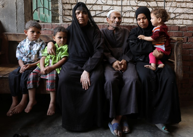 Family members of Youssef Abdullah, one of at least 22 Egyptians found dead earlier this month, perishing from heat and starvation after trekking the Libyan desert by foot, sit on a bench in the village of Tarfa al-Kom in Minya province, Egypt, July 12, 2017. Credit: Reuters/Mohamed Abd El Ghany