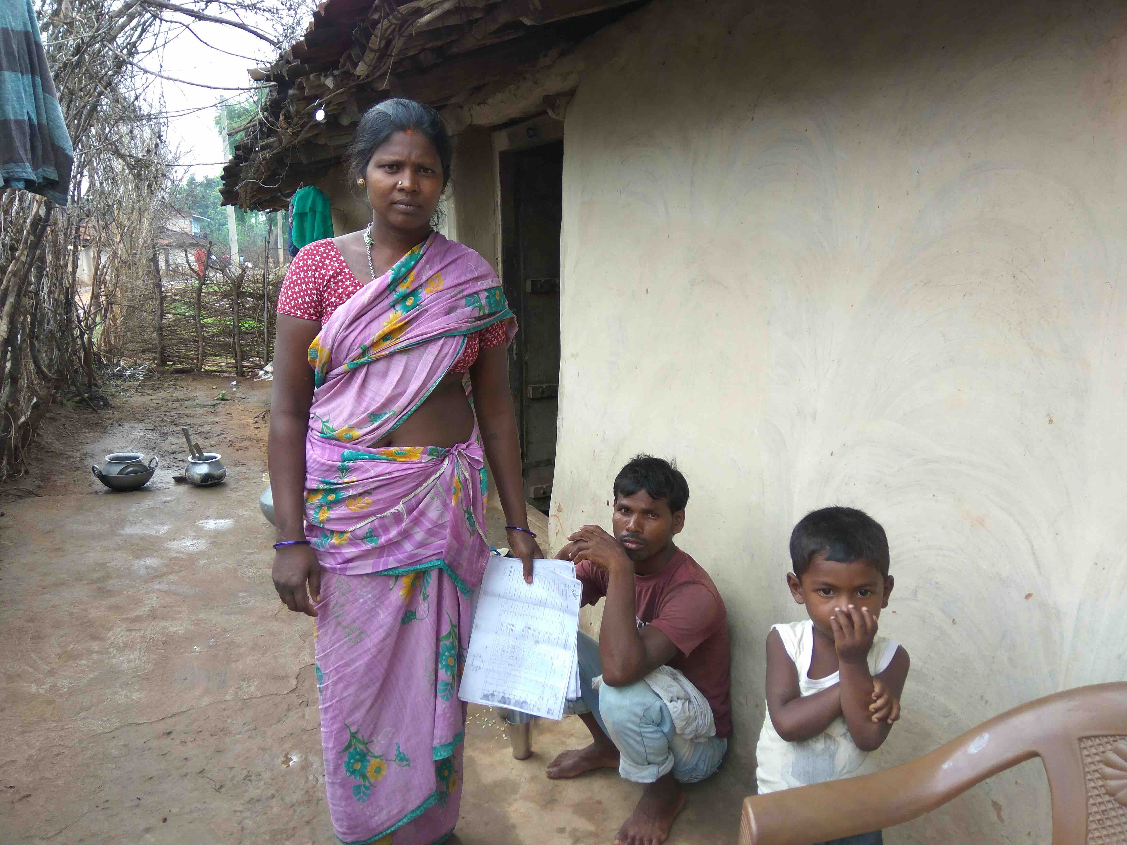Umesh Oraon, Manju Devi and their son outside their house. Manju Devi is holding the papers highlight how Umesh's wages are going to a different account. Credit: Jahnavi Sen