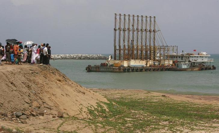 A group of Sri Lankan visitors at the new deep water shipping port watch Chinese dredging ships work in Hambantota, 240km (149 miles) southeast of Colombo, March 24, 2010. Credit: Reuters/Andrew Caballero-Reynolds/File Photo