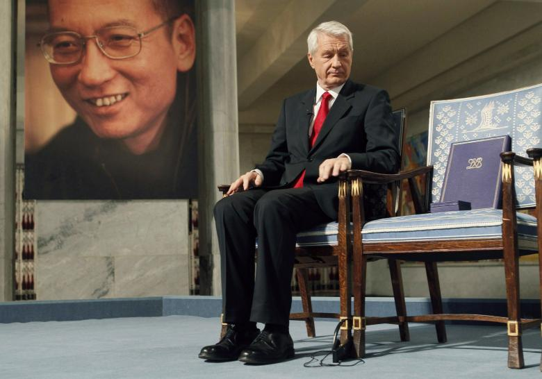 Chairman of the Norwegian Nobel Committee Thorbjoern Jagland looks down at the Nobel certificate and medal on the empty chair where Nobel Peace Prize winner Liu Xiaobo would have sat, as a portrait of Liu is seen in the background, during the ceremony at Oslo City Hall December 10, 2010. Credit: Reuters/Heiko Junge/Scanpix Norway/Pool