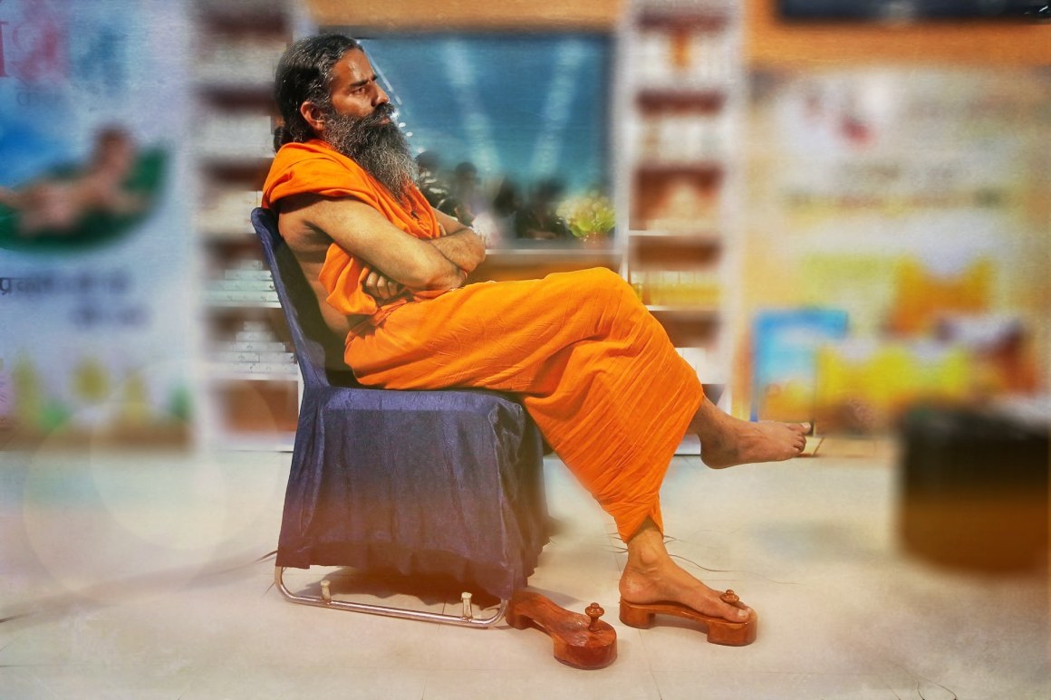 Baba Ramdev sits in front of a display of Patanjali products. Credit: Reuters/Adnan Abidi