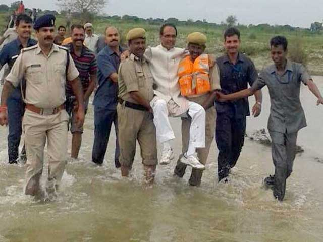 MP chief minister Shivraj Singh Chouhan being lifted by security officials in his visit to a flood-hit area. Credit: Twitter