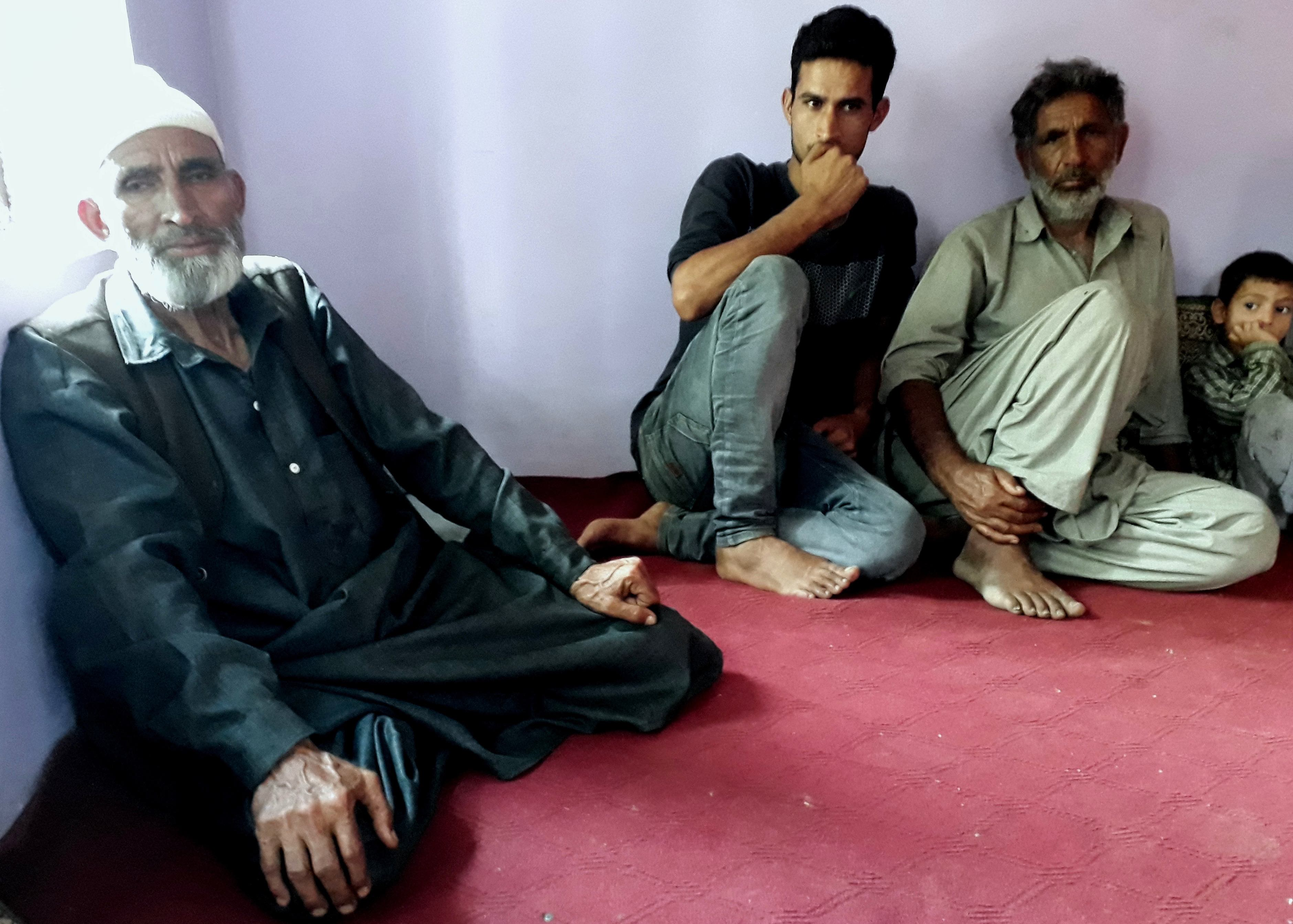From left: Father of Riyaz Ahmad, his son Aijaz and father of Shehzad discussing the army tribunal verdict. Credit: The Wire