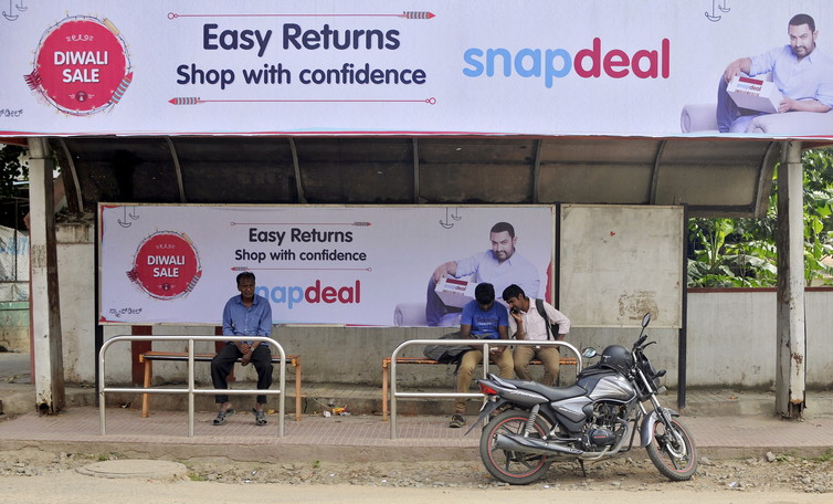 Commuters sit at a bus stop adorned with an advertisement of Indian online marketplace Snapdeal. Credit: Reuters/Abhishek Chinnappa