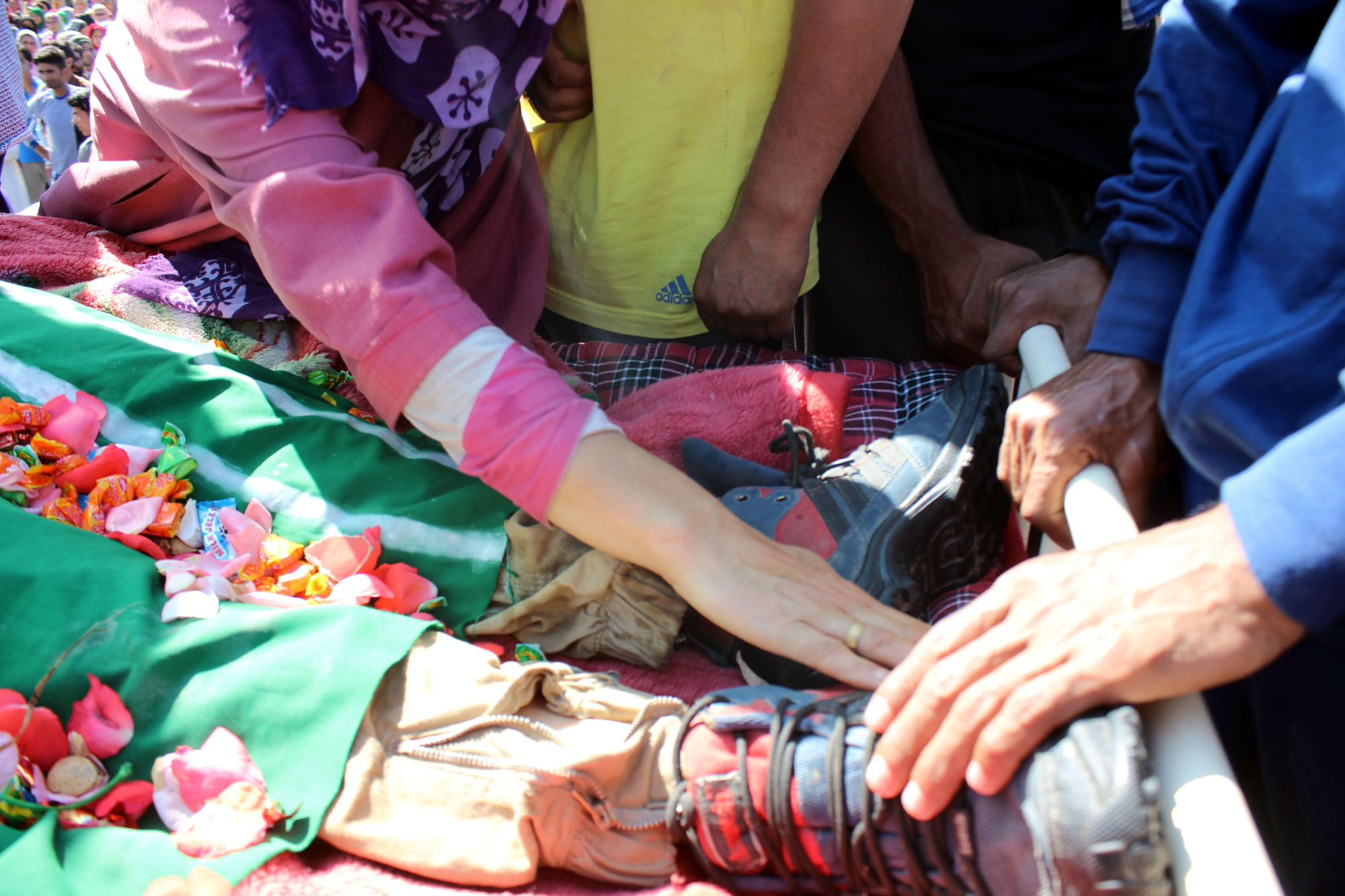 A local woman touches the feet of Bashir Lashkari at his funeral in Sopshali Kokernag. Credit: Vikar Syed