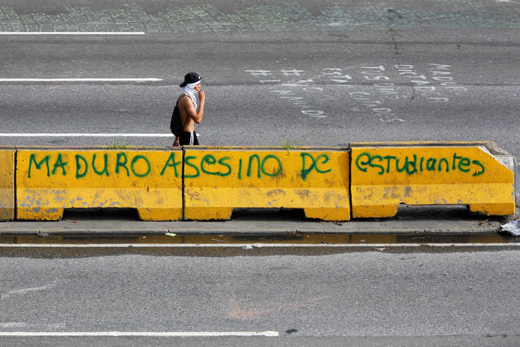 A protester passing grafitti that reads, 'Maduro, murderer of students'. Credit: Reuters/ Christian Veron