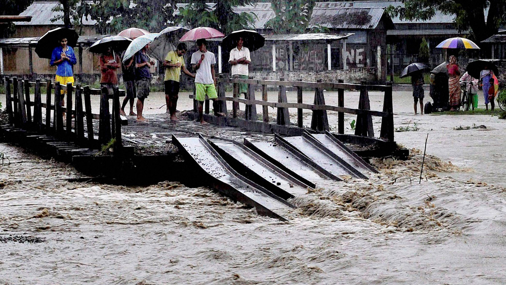 Villagers stand on a half-submerged wooden bridge in the flood hit Baska district, Assam. Credit: PTI