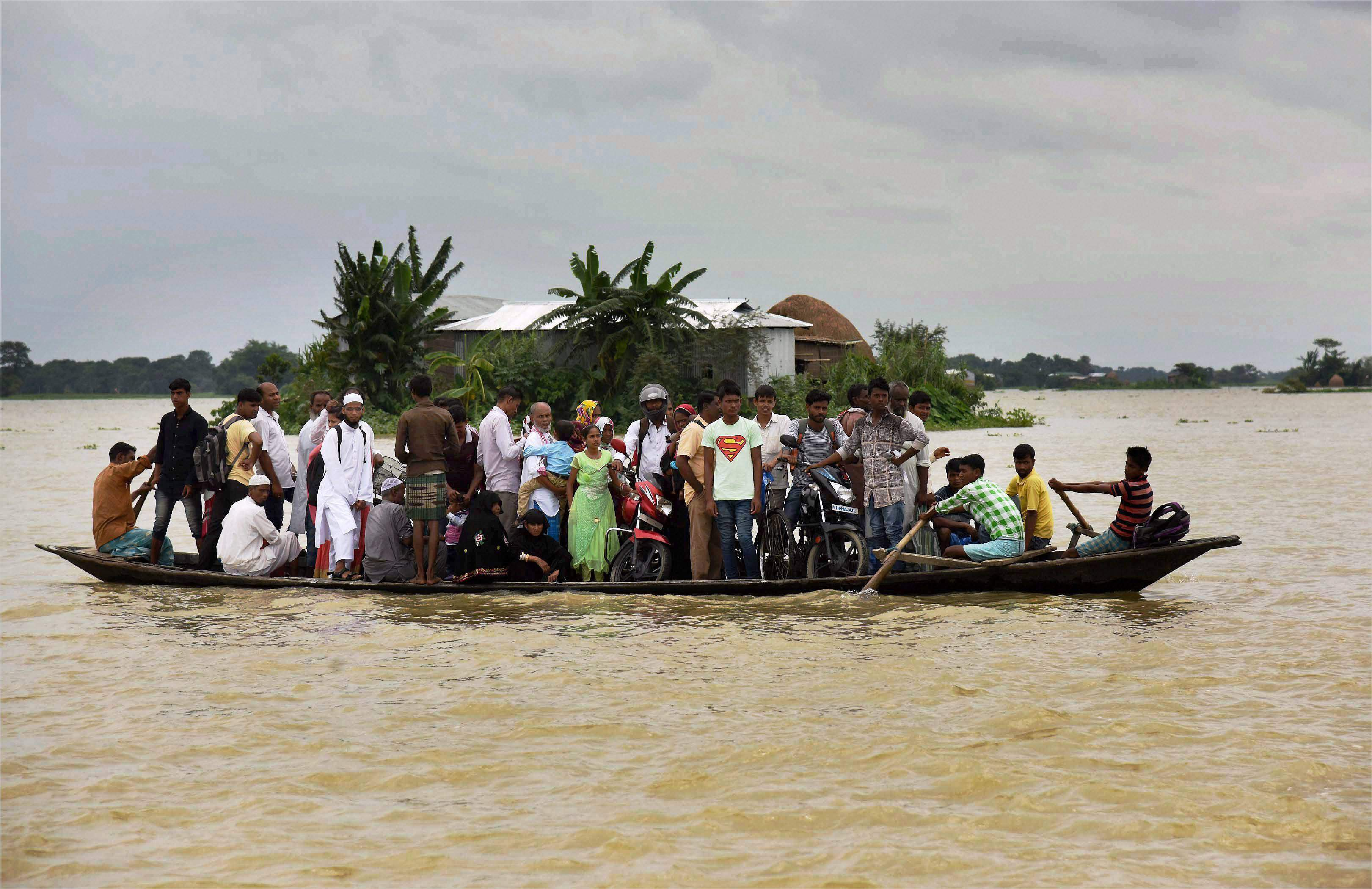 Affected villagers commute to safer places using a boat at Morigaon district in Assam. Credit: PTI