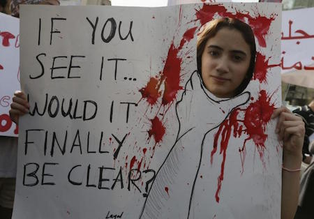 An activist holds a banner during a march against domestic violence against women, marking International Women's Day in Beirut, March 8, 2014. Credit: Reuters