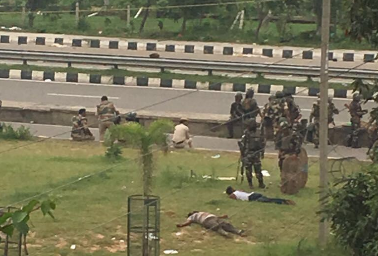 The police stand near bodies of two men killed in Panchkula following a violent riot by supporters of Gurmeet Ram Rahim Singh. Credit: Special Arrangement