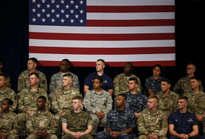 Military personnel watch as US President Donald Trump announces his strategy for the war in Afghanistan during an address to the nation from Fort Myer, Virginia, US, August 21, 2017. Credit: Reuters/Joshua Roberts