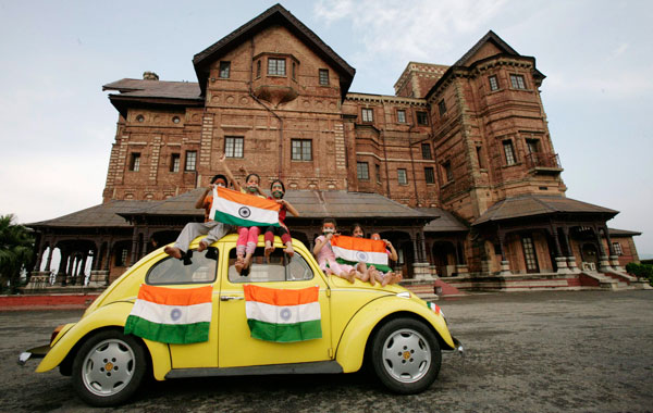 Children hold Indian national flags as they sit on a car during a photo-shoot in front of Hari Palace during the Independence Day celebrations in Jammu. Credit: Reuters