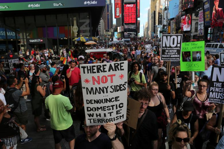"A protester holds a sign reading ""There are not 'many sides', Denounce domestic white terrorism"" at a march against white nationalism in Times Square in New York City. Credit: Reuters/Joe Penney"
