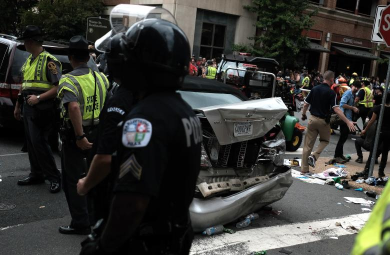 "First responders stand by a car that was struck when a car drove through a group of counter protesters at the ""Unite the Right"" rally Charlottesville. Credit: Reuters/Justin Ide"