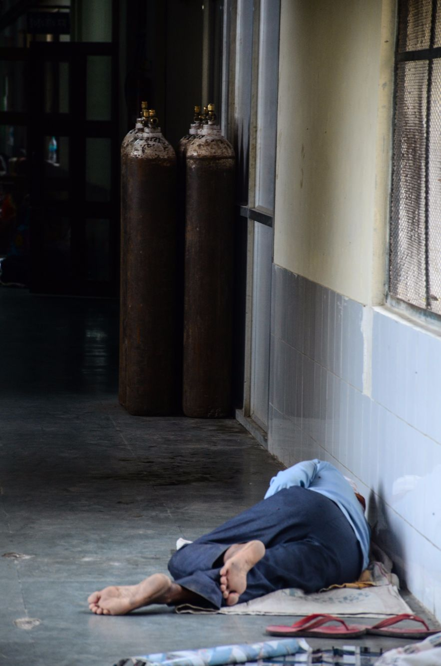 A man sleeping beside a group of oxygen cylinders, the lack of which was a major cause for the recent deaths in August