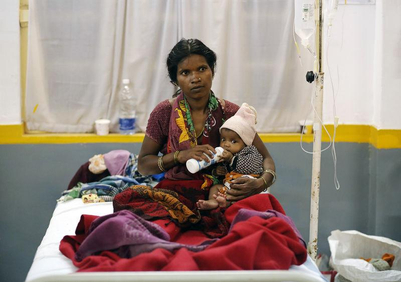 A woman, who underwent a sterilisation surgery at a government mass sterilisation camp, feeds her child while sitting on a hospital bed for treatment in Bilaspur, in Chhattisgarh November 14, 2014. Credit: Reuters/Anindito Mukherjee