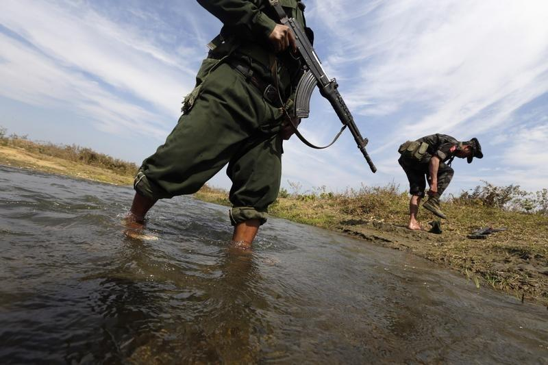 A soldier from the Kachin Independence Army (KIA) puts on his shoes as he and his comrade cross a stream towards the front line in Laiza, Kachin state, January 29, 2013. Credit: Reuters/David Johnson