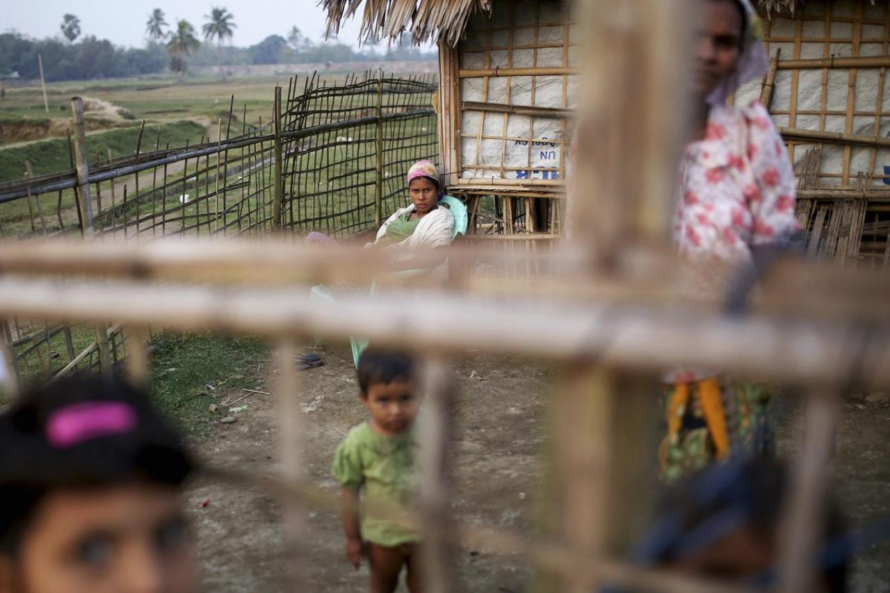 Internally displaced Rohingya women and children look from behind the fence of their temporary home at Thae Chaung IDP camp on the outskirts of Sittwe, February 15, 2015. Credit: Reuters/Minzayar