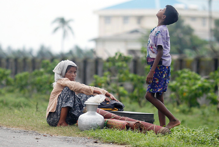 Rohingya people rest by the road with their belongings as they move from their village after violence in Sittwe, June 16, 2012. Credit: Reuters